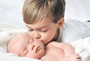Мальчик целует новорожденного малыша