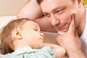 Мужчина смотрит на спящего ребенка