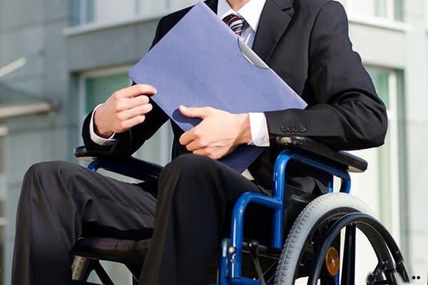 Мужчина в инвалидной коляске с папкой