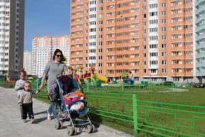 Мама гуляет с детьми возле новостроек