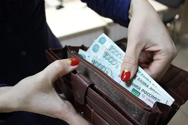 Женщина кладет деньги в кошелек