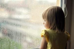 Девочка грустит у окна