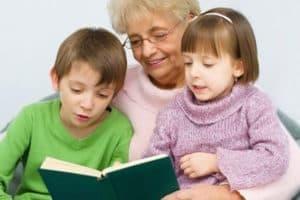 Бабушка читает книжку с внуками