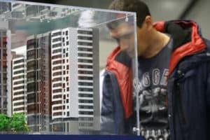 Молодой человек рассматривает макет многоэтажки