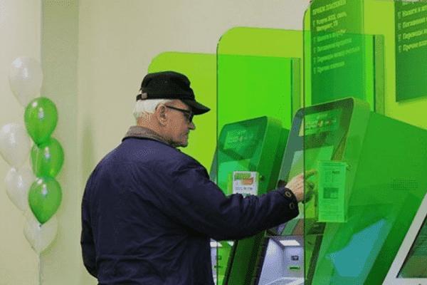 Пенсионер пользуется банкоматом Сбербанка