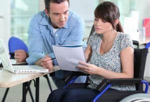 Женщина в инвалидном кресле читает документ